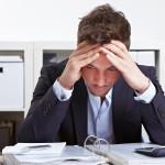 Mann mit Burnout über Akten gebeugt am Schreibtisch im Büro